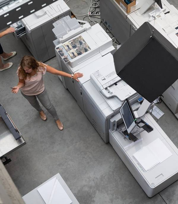 Woman standing next to a large printer