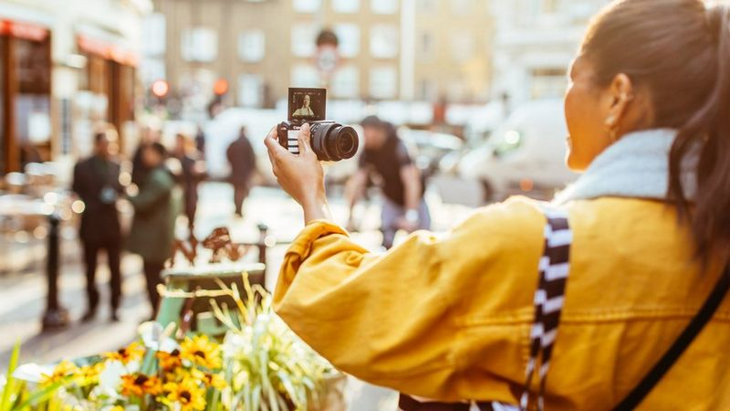 A young woman wearing a yellow jacket takes a selfie with the Canon M50 in a city environment.