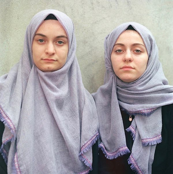 Two sisters wearing headscarves on their graduation from a Qur'an school in Kars, Turkey.