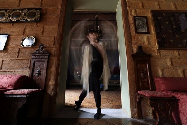 A dancer captured in a doorway of an ornately decorated room, arms blurred by motion.