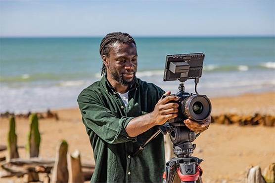 Against a serene beach backdrop, filmmaker Jolade Olusanya smiles as he studies his footage, filmed on the Canon EOS C70.