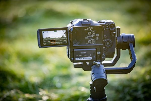 A Canon EOS C70 video camera mounted on a tripod.
