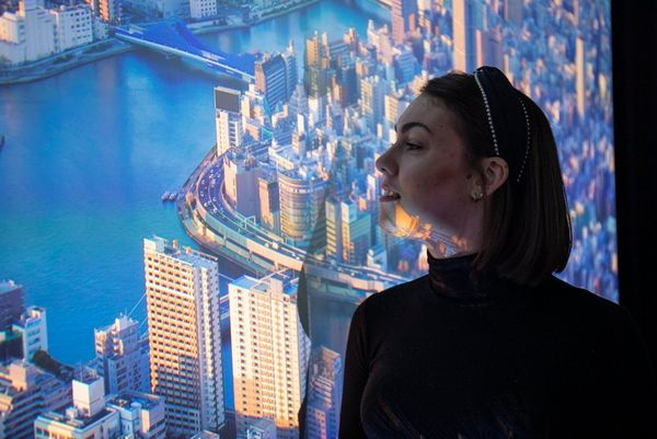 A side profile of a woman standing in front of an image of a city projected onto the wall.