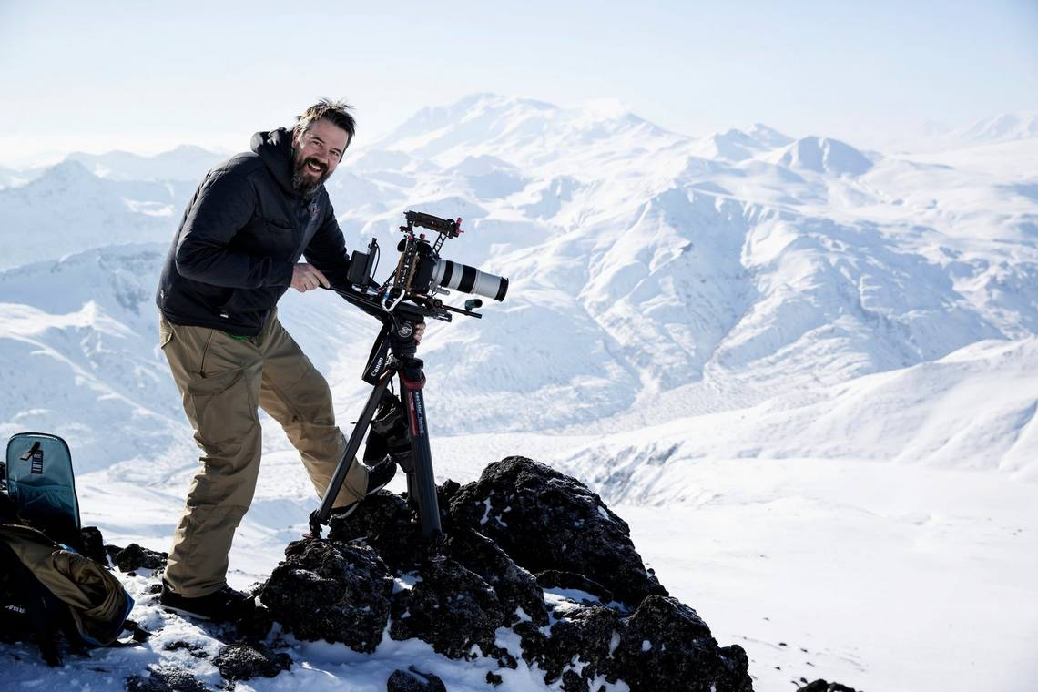 Alex Wykes with his fully rigged-up Canon EOS-1D X Mark III on top of a snowy mountain in Russia.