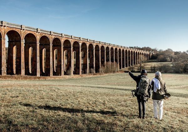 Two people stand in a valley looking at the Balcombe Viaduct in West Sussex, England.