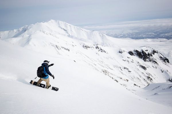 Alex Wykes snowboarding down a mountain carrying a Canon EOS-1D X Mark III.