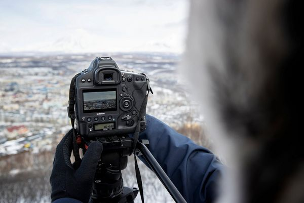 The rear screen of a Canon EOS-1D X Mark III being operated by a person wearing gloves in a snowy landscape.