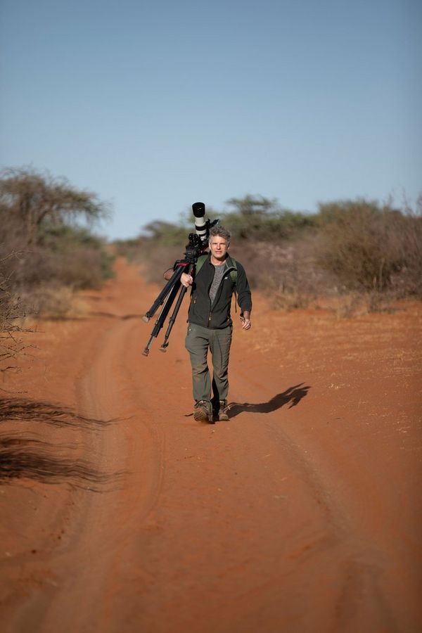 Camera operator Bosie Vincent carrying a Canon EOS-1D X Mark III, attached to a tripod, down a desert road.