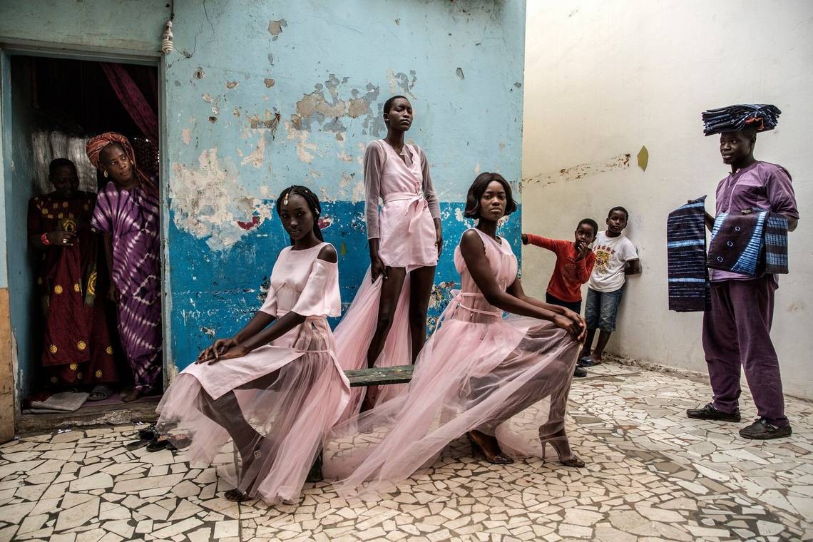 Three Senegalese models in flowing pink dresses show off a fashion line in front of a building in Dakar with flaking blue walls.