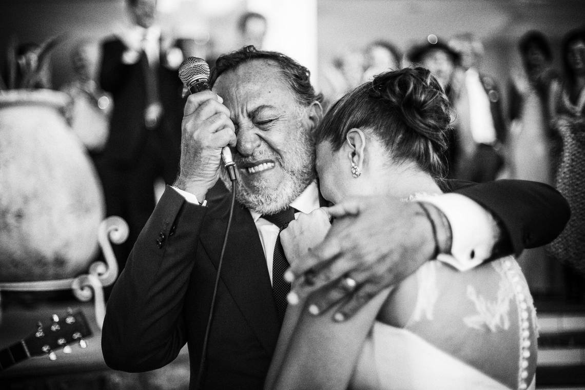 Arm around his newlywed daughter, a father is overcome with emotion while making a speech.