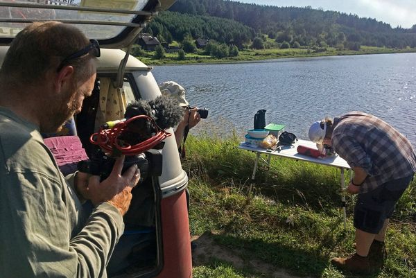 Clemens Boecker stands by the open tailgate of a VW campervan filming Joey Kelly cooking on a trestle table by a lakeside.
