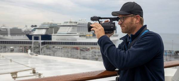 Clemens Boecker filming with a Canon XA55, with large cruise ships in the background.