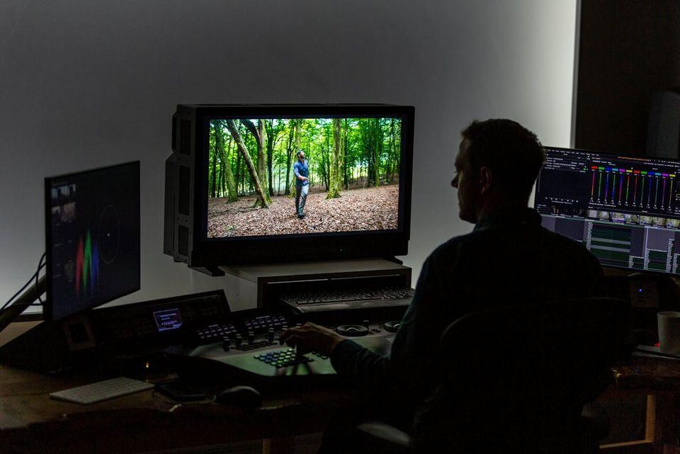 Un ordinateur dans une suite de montage vidéo avec deux écrans de référence HD.
