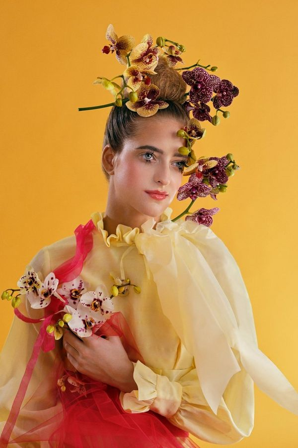 A model in front of a yellow background wearing large flowers on her head and neck.