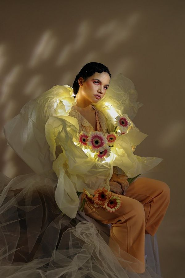 A portrait of a model wearing a yellow outfit covered with flowers.