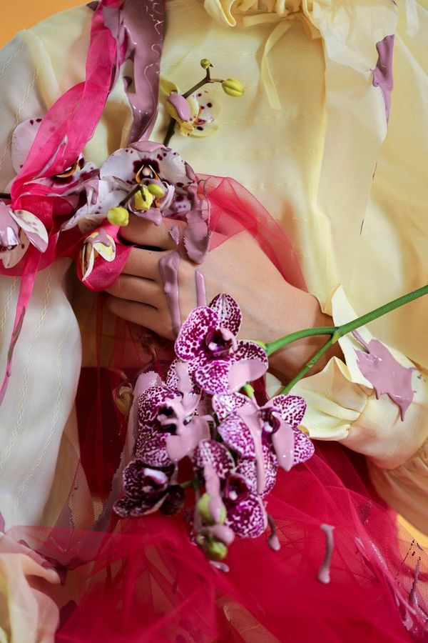 A close-up of a model's hands and torso, draped in flowers.