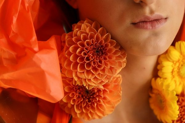 A close-up portrait of a model wearing flowers around her neck.
