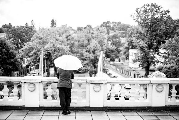 A man under an umbrella pictured from behind leaning on a stone parapet facing a tree-lined park.