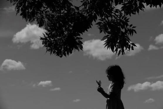 A black and white image of a girl in silhouette holding a butterfly.