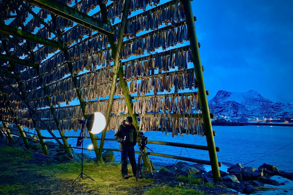 Roberto Palozzi, lit by a spotlight, films in the twilight inside a huge wooden frame covered in air-drying fish.