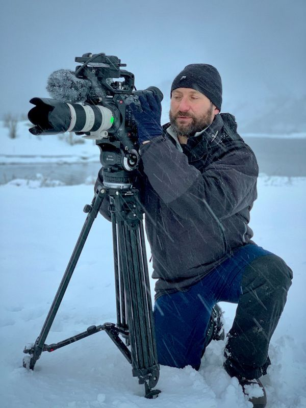 Roberto Palozzi kneels by an EOS C500 Mark II on a tripod in a snowstorm.