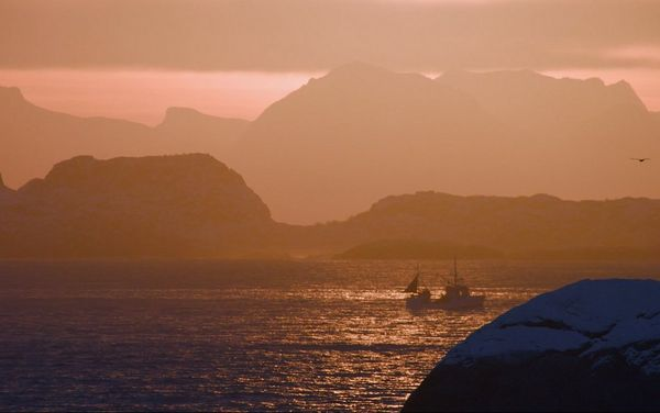 A fishing boat on the glistening water at dusk, with mountains silhouetted behind.