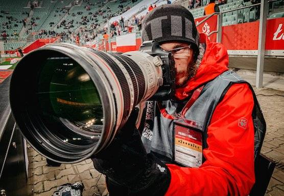 Photographer and Canon Ambassador Łukasz Skwiot with a large Canon lens.