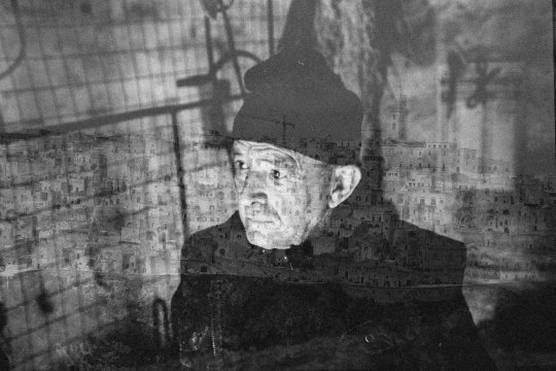 A black and white double exposure of an elderly man in a hat and a cityscape of old stone buildings.