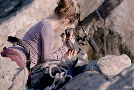A video still showing journalist and cinematographer Elisa Iannacone filming with the Canon XA55 camcorder while cliff camping in Wales.