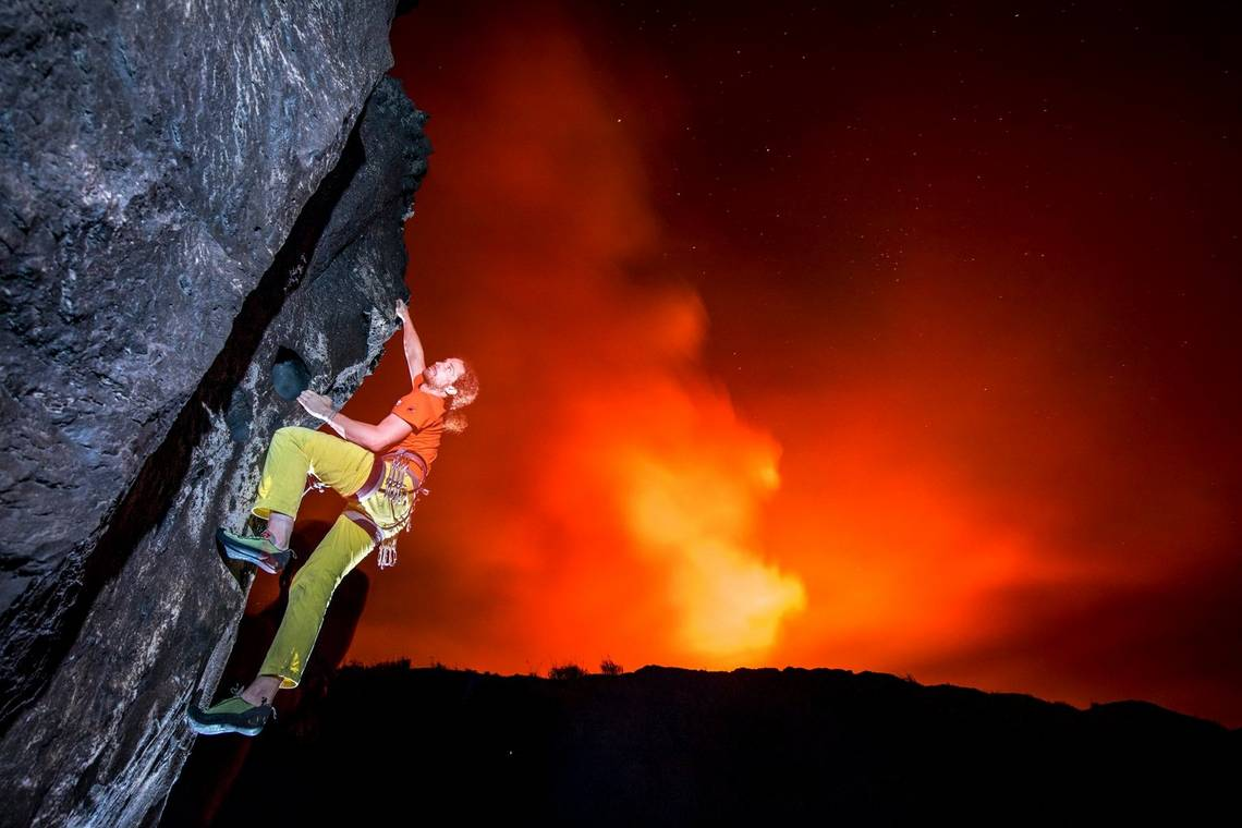 A rock climber scaling the side of an active volcano, with the red glow of the caldera behind.