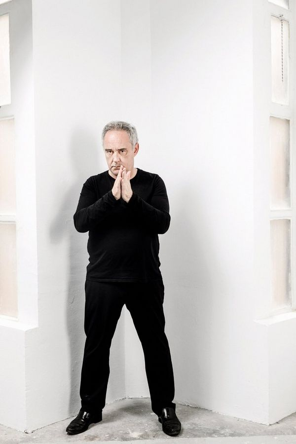 A portrait of Spanish Chef Ferran Adrià dressed in black and standing against a white wall.