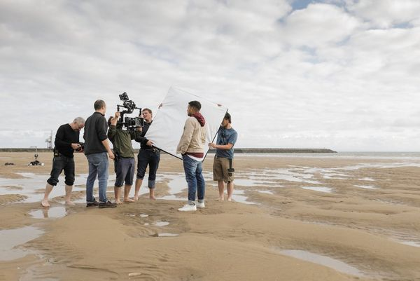 A group on a beach seen from a distance, with one filming with a camera in a gimbal while two others hold a large reflector.