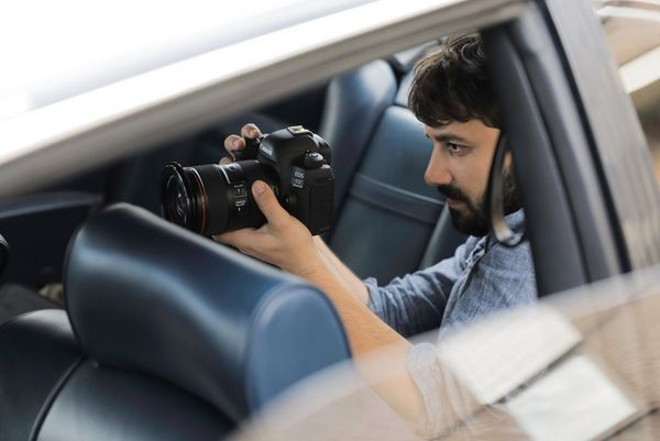 Cinematographer Christian Anderl in the rear seat of a motor car, filming with a Canon EOS 5D Mark IV.