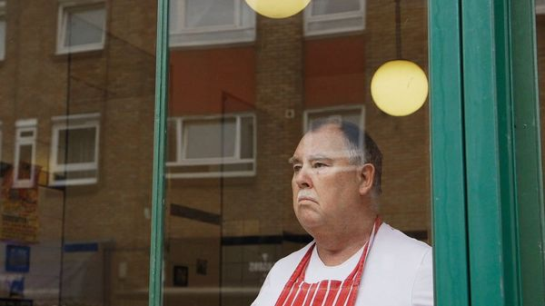 The owner of a pie and mash shop, wearing a red apron, looks out of his shop window. A film still from Zed Nelson's The Street.