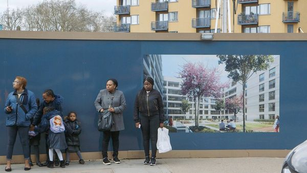 People standing on the pavement in front of a billboard advertising new luxury apartments that are being built. A film still from Zed Nelson's The Street.
