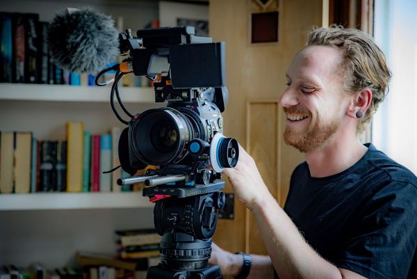 Cinematographer Steve Turvey, smiling, adjusts settings on a Canon EOS C300 Mark II camera on a tripod.