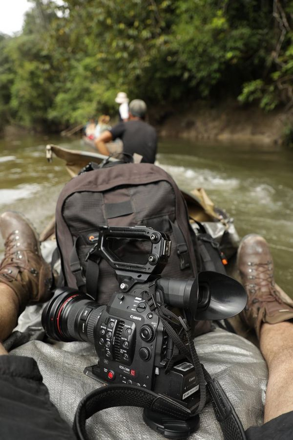 A Canon EOS C300 Mark II sits between a man's legs in a canoe on a river through dense jungle.