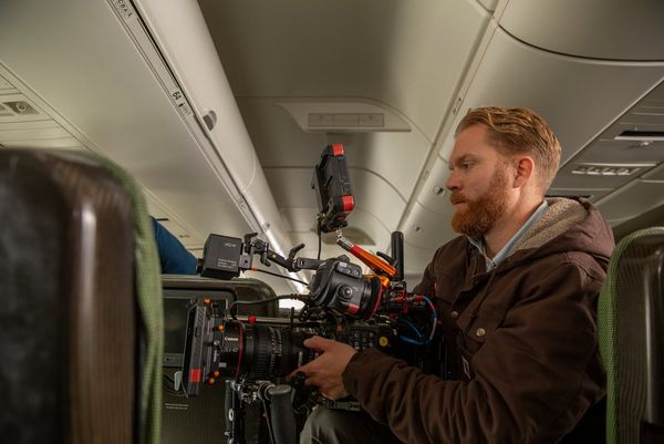 Steve Holleran filming with a Canon EOS C300 Mark III inside the cabin of an aircraft.