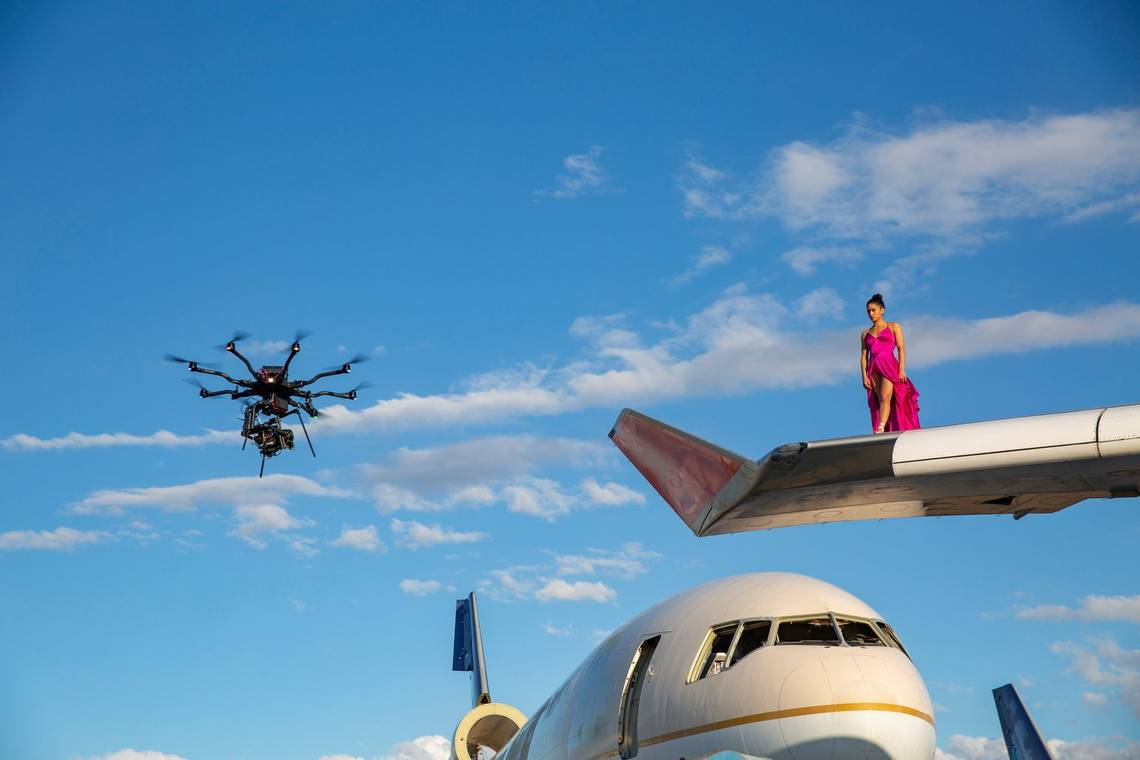 A Canon EOS C300 Mark III attached to a drone, filming a ballerina in a bright fuchsia dress standing on the wing of a 747.
