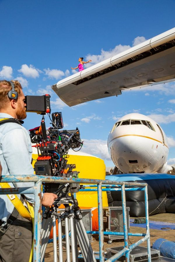 Cinematographer Steve Holleran filming with a Canon EOS C300 Mark III from the ground, looking up at the wing of an aircraft.