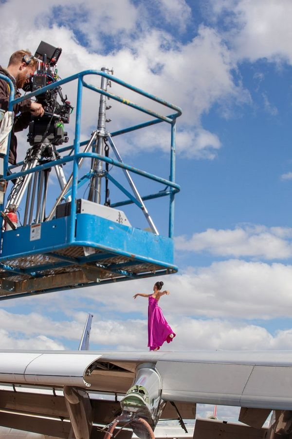 A ballerina dancing on the wing of an aircraft being filmed by a cameraman on a forklift.
