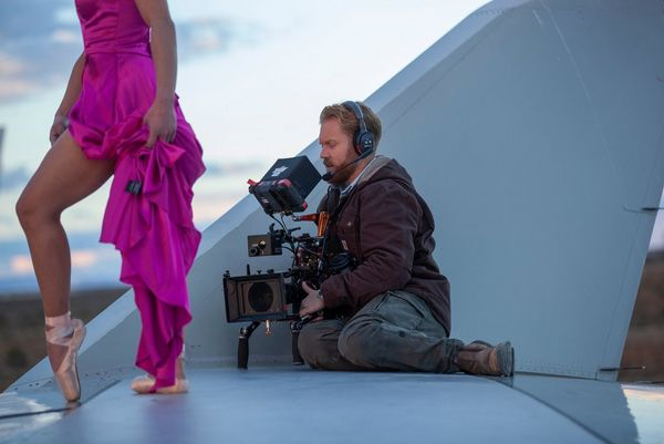 A cameraman with a Canon EOS C300 Mark III sat on the wing of an aircraft filming a ballerina dancing next to him.