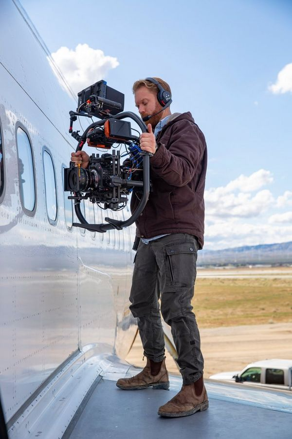 Cinematographer Steve Holleran stands on the wing of an aircraft holding a Canon EOS C300 Mark III on a gimbal and films through the window.