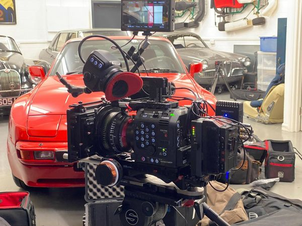 A Canon EOS C500 Mark II set up for filming in an auto shop in front of a red car.