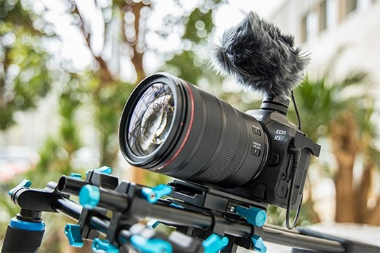 A Canon EOS R5 fitted with a microphone, attached to a filming rig.