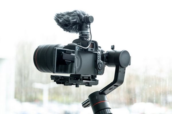 A Canon EOS R5 mounted on a filming arm mount with an external microphone.