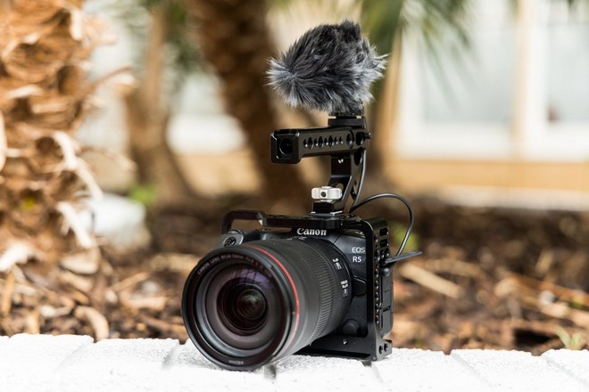 A Canon EOS R5 rigged for filming with an external microphone mounted on top of the rig.