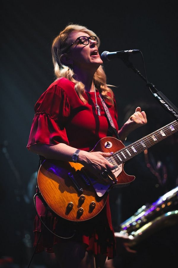 A woman wearing a red dress and holding a guitar sings into a microphone.