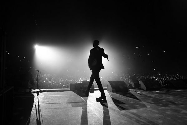 A black-and-white shot of Liam Payne silhouetted against the stage lights while performing at Wembley Arena.