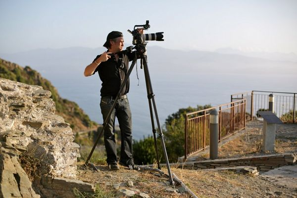 Sébastien Devaud working on location, positioning his Canon kit on a tripod by the coast.